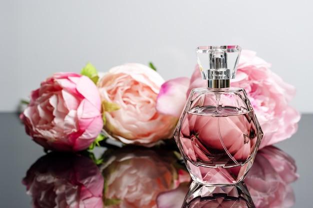 Flacon de parfum rose avec des fleurs sur une surface en noir et blanc