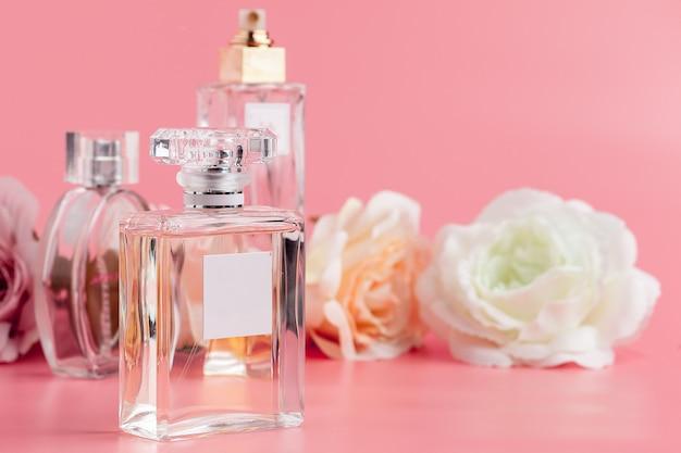 Flacon de parfum avec des roses sur du tissu rose