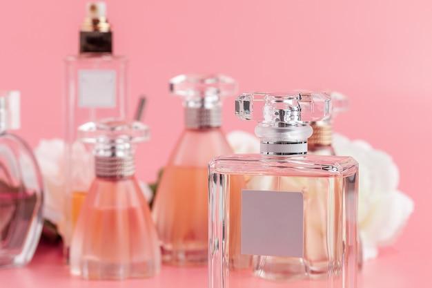 Flacon de parfum avec des roses sur tissu rose