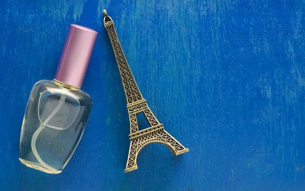 Un flacon de parfum et une statuette souvenir de la tour eiffel sur fond bleu.