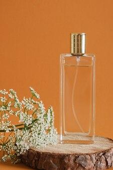 Flacon de parfum sur une surface en bois sur fond marron, podium en bois et fleur