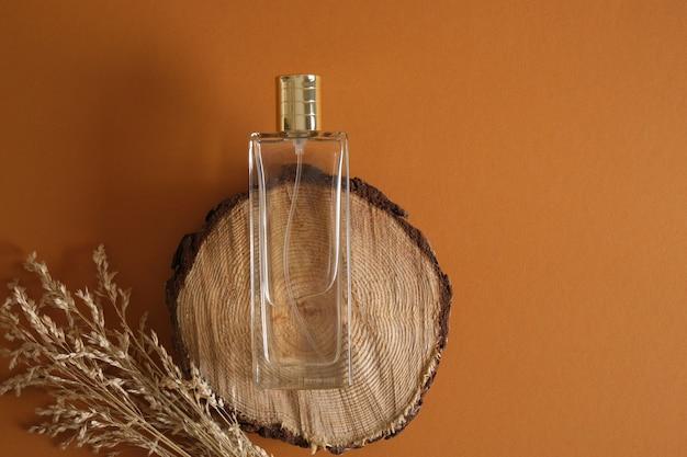 Flacon de parfum sur la surface en bois sur la vue de dessus de fond marron