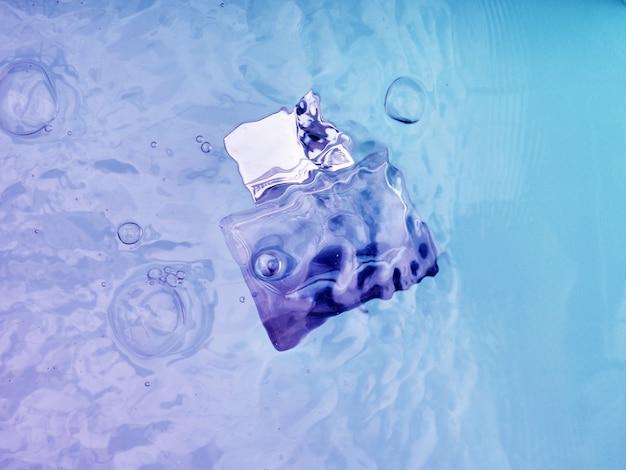 Flacon de parfum transparent bleu sous l'eau, vagues au-dessus.