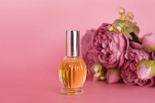 Flacon de parfum transparent avec bouquet de pivoines sur fond rose. bouteille d'essence aromatique