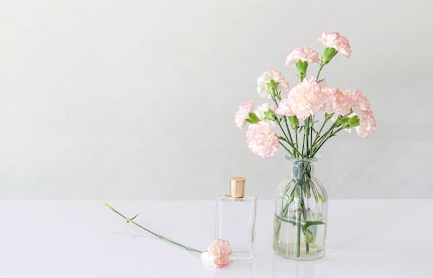 Flacon de parfum avec vase de fleurs d'oeillets sur table blanche.