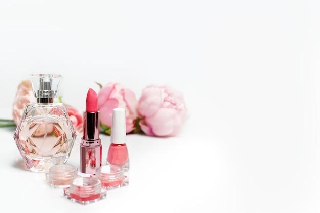 Flacon de parfum, vernis à ongles, rouge à lèvres et fleurs sur une surface blanche