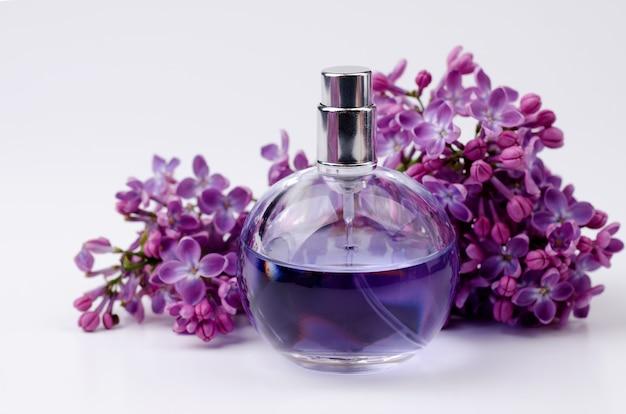 Flacon de parfum en verre en composition avec branche de fleur de lilas aromatique