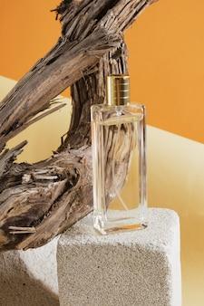 Flacon de parfum en verre sur un podium en béton, sur fond de bois flotté, fond d'ombre naturelle