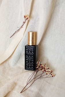 Flacon de parfum vintage arabe avec fleurs séchées sur tissu en coton naturel.