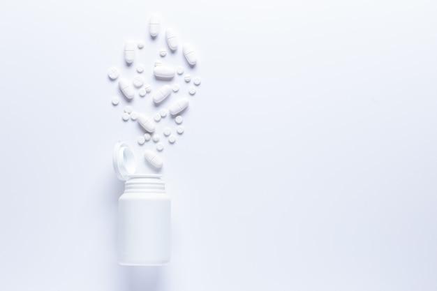 Flacon de pilules renversé avec comprimés