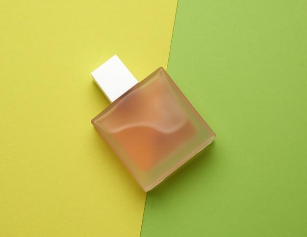 Flacon plein rose avec un parfum de verre dépoli se trouve sur un espace coloré