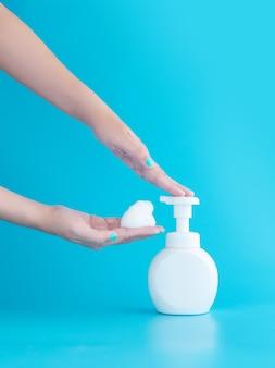 Flacon pompe en plastique et mousse mousse ou mousse nettoyante sur main de femme isolée sur fond bleu, vertical avec espace copie. concept de nettoyage