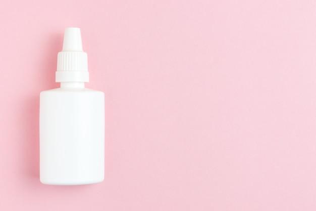 Flacon pulvérisateur nasal sur fond rose. design plat avec espace de copie.