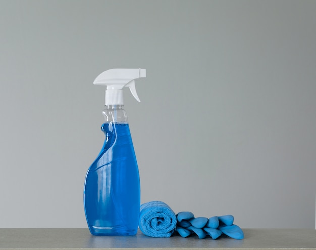 Flacon pulvérisateur de nettoyage bleu avec distributeur en plastique, soucis et chiffon pour éliminer la poussière sur fond gris