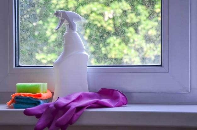 Flacon pulvérisateur avec nettoyant, chiffon, éponge de nettoyage se trouve sur le rebord de la fenêtre sur fond de fenêtre sale