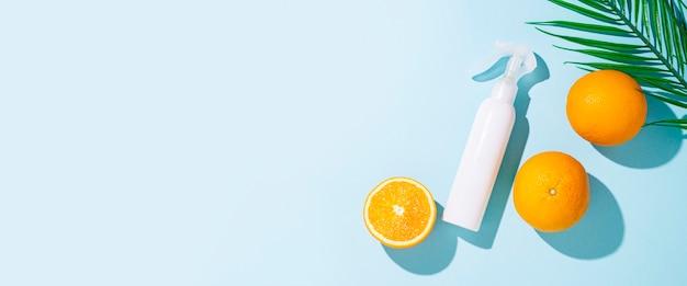 Flacon pulvérisateur, oranges et feuille de palmier . vue de dessus, mise à plat. bannière
