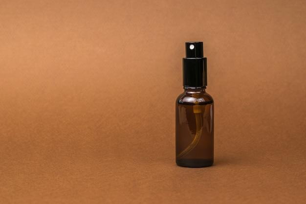 Flacon pulvérisateur en verre sur fond marron.