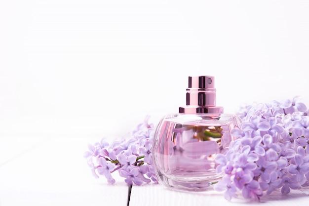 Flacon rose de parfum pour femme avec des fleurs lilas sur mur blanc