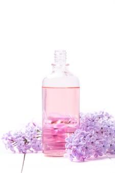 Flacon rose de parfum pour femme avec des fleurs lilas sur un mur en bois blanc