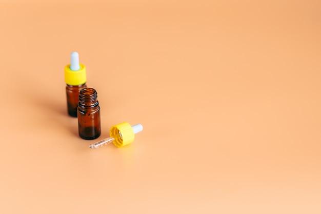 Flacon de sérum compte-gouttes en verre sur fond orange