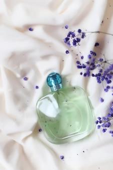 Flacon de sérum avec des fleurs de lilas sur le lit