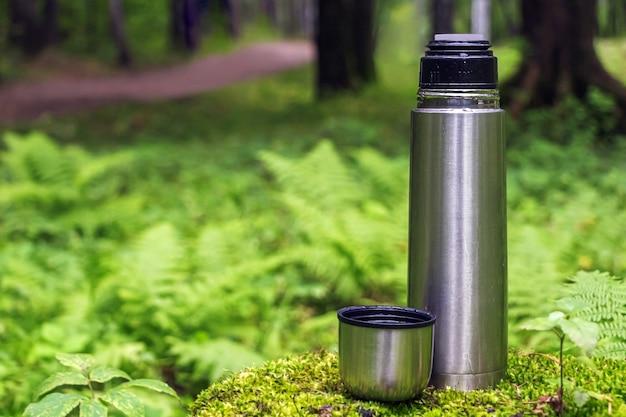 Flacon thermos en acier inoxydable ouvert avec boisson au thé sur souche dans la forêt de conifères