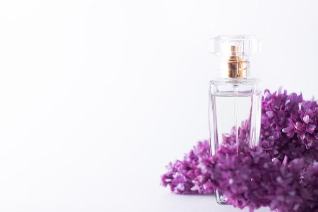 Un flacon transparent de parfum en fleurs lilas violettes printanières fraîches