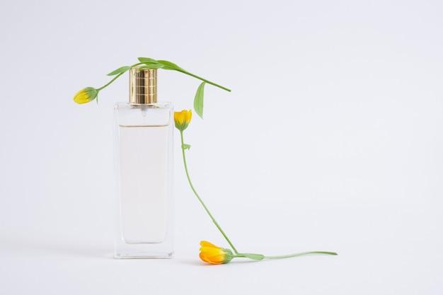 Flacon transparent de parfum sur fond gris. couvercle en verre transparent et métal cuivre.