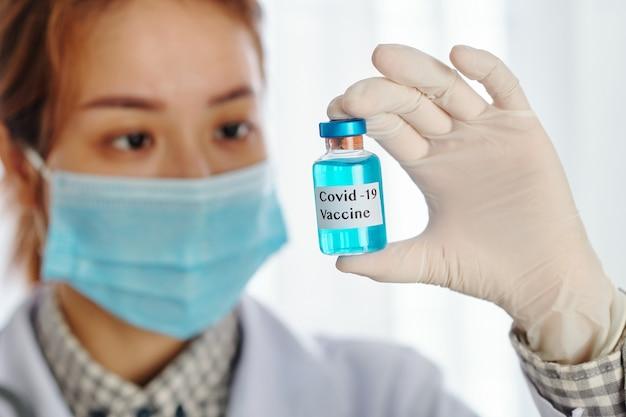 Flacon de vaccin bleu covid-19 entre les mains d'un jeune travailleur de laboratoire asiatique sérieux