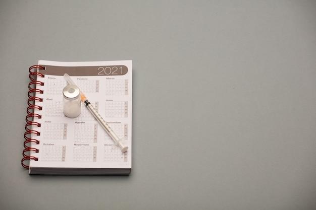 Flacon de vaccin, avec calendrier 2021 et seringue, fond gris