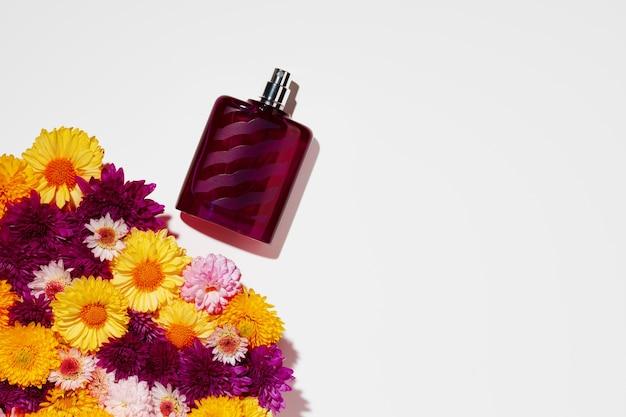 Flacon vaporisateur de parfum et petites fleurs sur fond gris