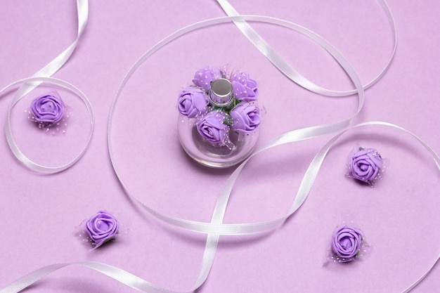 Flacon vaporisateur de parfum avec petites roses lilas et ruban de satin blanc. parfum comme cadeau pour femme