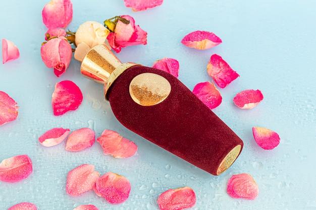 Flacon en velours au parfum féminin. entouré de pétales de rose sur un espace lumineux.
