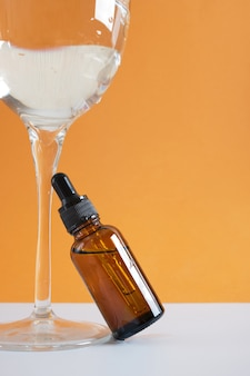 Flacon en verre ambré avec une pipette et un verre d'eau sur fond marron, flacon compte-gouttes pour huile cosmétique ou sérum