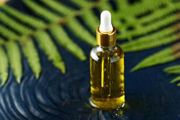 Flacon en verre compte-gouttes avec de l'huile cosmétique jaune sur l'eau avec des feuilles vertes fougère sur fond bleu classique