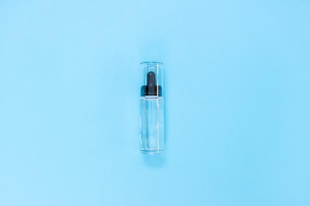 Flacon en verre compte-gouttes. pipette cosmétique sur bleu. mise à plat