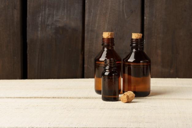 Flacon en verre cosmétique avec bouchon en liège. bouteilles brunes sur une table blanche contre un mur en bois foncé
