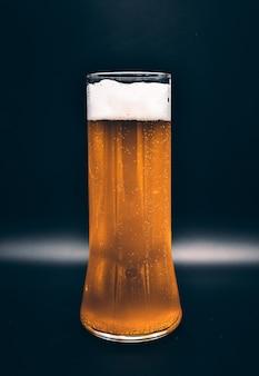 Flacon en verre sur fond noir avec liquide jaune et mousse blanche, un verre de bière sur fond noir