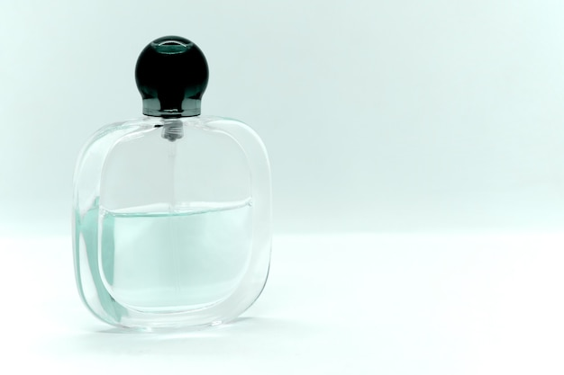 Flacon en verre de parfum couleur émeraude pâle et espace pour le texte.