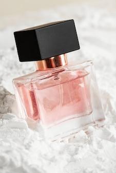 Flacon en verre de parfum féminin sur poudre texturée