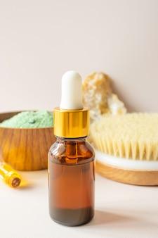 Flacon en verre avec pipette, bougie, petite bouteille d'huile essentielle, pinceau naturel et pierre décorative sur espace lumineux. le concept des procédures cosmétiques dans la salle de bain, le bain à vapeur, le sauna.