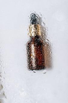 Flacon en verre avec pipette avec des gouttes dessus