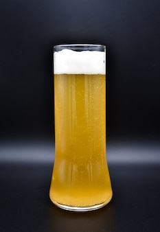 Flacon en verre sur une surface noire avec un liquide jaune et une mousse blanche, un verre de bière