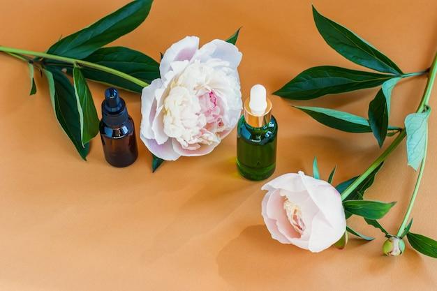 Flacon en verre vert avec huile parfumée de pivoine de luxe. concept de soins de la peau.