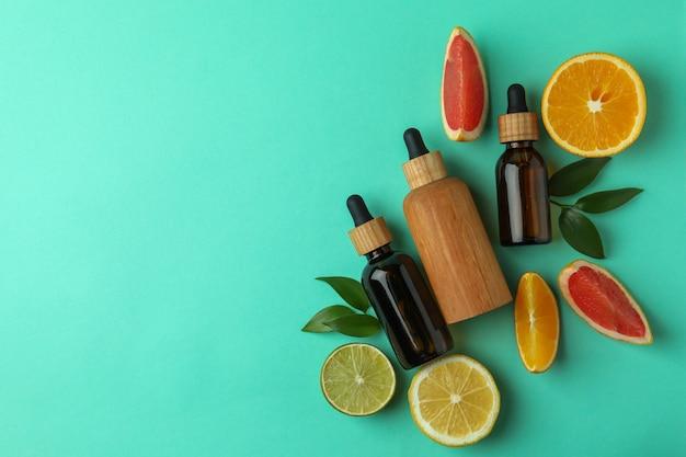 Flacons compte-gouttes avec de l'huile et des agrumes sur fond isolé de menthe