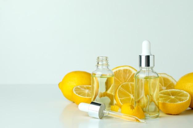 Flacons compte-gouttes avec de l'huile et des citrons sur tableau blanc