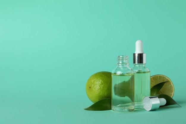 Flacons compte-gouttes avec de l'huile et des citrons verts sur fond de menthe