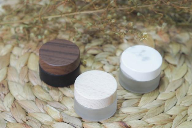 Flacons cosmétiques contenant des produits blancs, bruns et crème à la fleur sèche.
