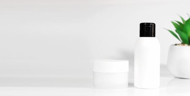 Flacons de cosmétiques de soins de la peau sur fond blanc, avec une plante verte. cosmétiques de printemps