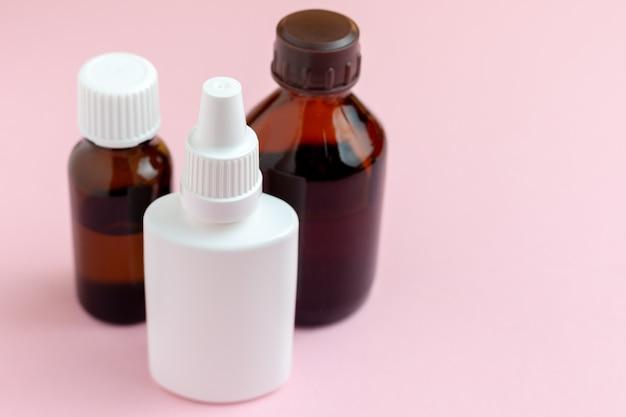 Flacons de médicaments clairs isolés sur fond rose. ensemble de médicaments